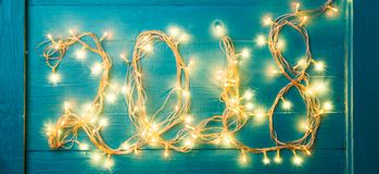 Photo of burning garland in form of number 2018. On blue table Royalty Free Stock Image