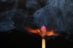 Photo of burning match. Photo of a burning match with smoke on a black background Royalty Free Stock Image