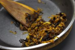 A photo of burnt onion on the teflon pan and wooden spatula. Spoiled unhealthy overcooked burned meal. Onion disgusting leftovers. Messthetics aesthetic Stock Photos