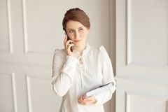 Photo business woman wearing suit, looking smartphone and holding documents in hands stock photo