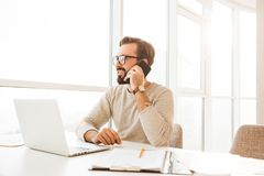 Photo of businesslike man 30s in casual clothing enjoying talkin. G on cell phone while working at home Stock Photo