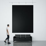 Photo of businessman in gallery. Waching empty black canvas hanging on the brick wall and generic design sofa concrete Stock Images