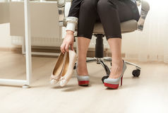 Photo of businesswoman changing shoes under table Stock Images