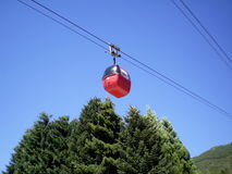 Photo of cable car on trees. You can see the blue sky and a mountain Stock Photography