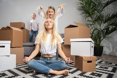 Photo of calm blonde sitting on floor among cardboard boxes and boy, girl jumping on sofa stock images