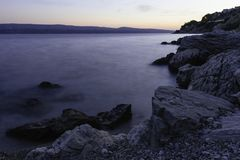 Photo of Calm Body of Water Beside Rock Formations Royalty Free Stock Photo