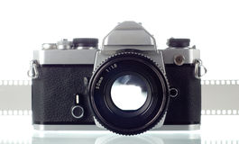 Photo camera. 35 mm film camera with negative strip in background Stock Images