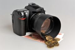 Photo camera with coins and banknotes on gray Royalty Free Stock Photography