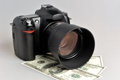 Photo camera with dollars on gray Stock Image