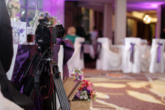 Photo camera at event. Photo camera and professional tripod in a ballroom for weddings Royalty Free Stock Images