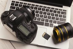 Photo camera, lens and memory card on computer. Keyboard closeup. Professional photographic equipment, modern technology for hobby or occupation, copy space stock image