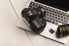 Photo camera, lens and memory card on computer. Keyboard closeup. Professional photographic equipment, modern technology for hobby or occupation, copy space royalty free stock images