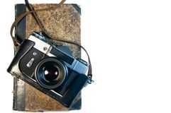 Photo camera and old book on white background isolated stock photography