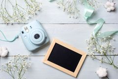 Photo camera and picture frame on blue wooden table. Spring minimal flowers frame, pastel colors, flat lay style, top view. Beauty. Technology concept, fashion stock photo