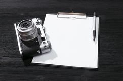 Photo camera. Shot list mockup. Photo session contract template. Vintage film photo camera and blank paper page on black wooden table background. Top view photo royalty free stock photography