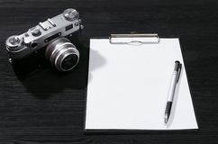 Photo camera. Shot list mockup. Photo session contract template. Vintage film photo camera and blank paper page on black wooden table background. Top view photo stock photos