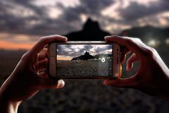 Photo camera of a smartphone. Taking photograph of Ipanema beach. Rio de Janeiro city at night.