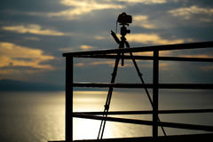 Photo camera on tripod. Dark silhouette at viewpoint on cloudy sky over sea on evening Royalty Free Stock Images