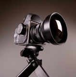 Photo camera with tripod on grey in Hi-Res Royalty Free Stock Photo