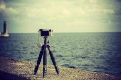 Photo camera on tripod in nature. Photography objects and equipment. Photo camera on small tripod taking picture of nature Stock Image