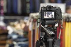 Photo camera on tripod recording video in clothing store. Photo camera recording video in clothing store stock photography