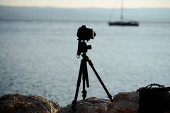 Photo camera on tripod. At rocky beach with sailboat yacht in blue sea on seascape background Royalty Free Stock Photos