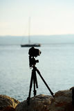 Photo camera on tripod. At rocky beach with sailboat yacht in blue sea on seascape background Royalty Free Stock Photography