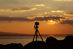 Photo camera on tripod. Photo camera silhouette on tripod at rocky beach with beautiful sunset in blue sea on seascape background Royalty Free Stock Photography