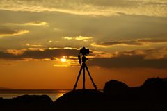 Photo camera on tripod. Photo camera silhouette on tripod at rocky beach with beautiful sunset in blue sea on seascape background Royalty Free Stock Images