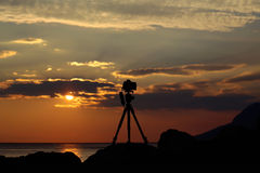 Photo camera on tripod. Photo camera silhouette on tripod at rocky beach with beautiful sunset in blue sea on seascape background Stock Image