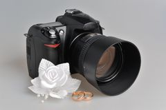 Photo camera, wedding boutonniere, rings on gray Royalty Free Stock Images