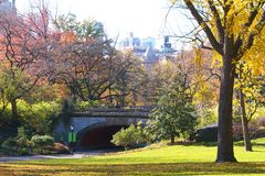 Winterdale Stone Arch Bridge at Central Park, NYC. Photo captures the beauty of the fall leaves as you walk through the park towards the Winterdale Arch. The sun Royalty Free Stock Photo