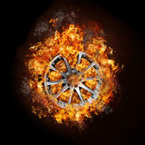 Photo of a car wheel on burning fire. With black background Stock Photo