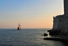 The fortification and the caravel. Photo of a caravel leaving Dubrovnik at dusk - Croatia - July 2010 Royalty Free Stock Image