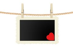 Photo card with red heart hanging on rope on white Stock Images