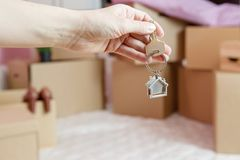 Photo of cardboard boxes, man`s hand with keychain, open door in new apartment. Blurred Background Royalty Free Stock Images