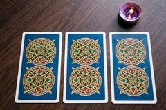 Photo of tarot card. Photo cards for fortune telling or playing. Tarot cards on a wooden background. With a burning candle Royalty Free Stock Image