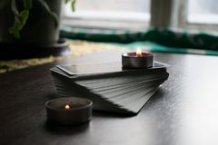 Photo of tarot card. Photo cards for fortune telling or playing. Tarot cards on a wooden background. With a burning candle Royalty Free Stock Photo