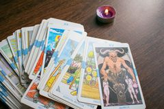 Photo of tarot card. Photo cards for fortune telling or playing. Tarot cards on a wooden background. With a burning candle Royalty Free Stock Photos