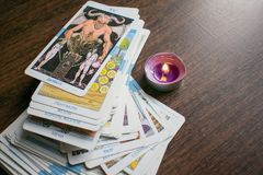 Photo of tarot card. Photo cards for fortune telling or playing. Tarot cards on a wooden background. With a burning candle Royalty Free Stock Images