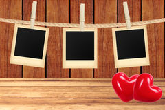 Photo cards hanging on rope on clothespins and two red hearts Stock Photos