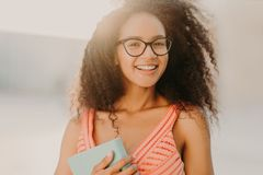 Photo of carefree African American student in summer dress, holds book, prepares for exam, strolls across city streets, enjoys. Warm sunny day, has charming royalty free stock photos