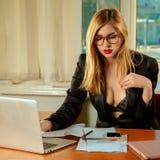 Photo carrée d'ordinateur portable fonctionnant de secrétaire sexy dans un bureau Photos libres de droits