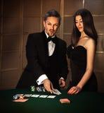 Photo carrée des couples sexuels dans le costume élégant pour jouer au poker photo stock