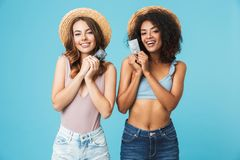 Photo of caucasian and african american women 20s wearing straw. Hats and swimsuits smiling and holding credit cards over blue background stock photography