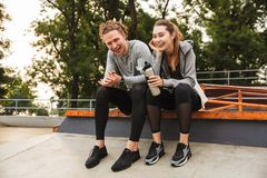 Photo of caucasian athletic couple guy and girl 20s in tracksuit Stock Photography