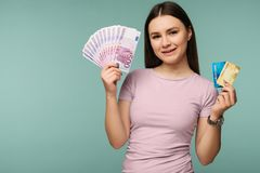 Photo of caucasian brunette woman 20s smiling while holding credit card and fan of euro cash isolated over blue background stock photo