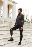 Photo of caucasian disabled woman in sportswear with prosthetic. Leg standing at the stairs and looking aside outdoor stock photography