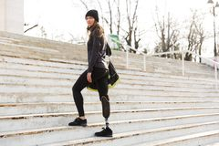 Photo of caucasian disabled woman in sportswear with prosthetic. Leg walking up the stairs outdoor stock photo