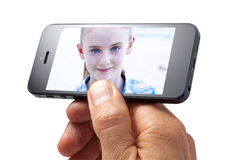 Photo Cell Phone Girl Hand. A hand holding a cell or mobile phone with a photo of a young girl on the screen isolated on a white background Royalty Free Stock Photos